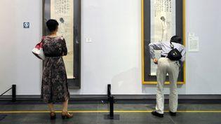 Des visiteurs face aux peintures de Wang Mengbai (gauche) et Qi Baishi, à l'occasion d'une ecposition consacrée aux maîtres de la peinture chinoise à Guangzhou, en mars 2014.  (LIANG XU / XINHUA)
