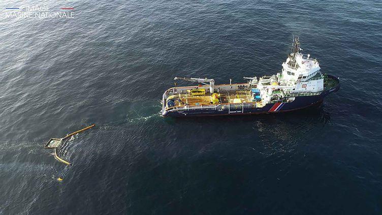 """Un navire de la Marine nationale installe une bouée pour contenir le pétrole du """"Grande America"""", le 22 mars 2019. (HANDOUT / MARINE NATIONALE / AFP)"""