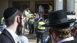 Des juifs ultra-orthodoxes devant la synagogue où a été perpétrée l'attaque, dans le quartier ultra-orthodoxe de Har Nof, à Jérusalem(Israël), le 18 novembre 2014. (JACK GUEZ / AFP)