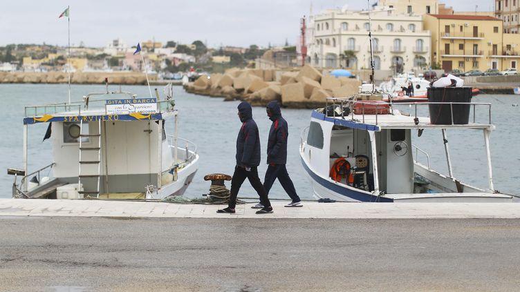 Deux migrants se promènent sur le port de Lampedusa (Italie), le 19 février 2015. (ALESSANDRO BIANCHI / REUTERS)