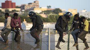 Des migrants africains tentent de franchir la barrière qui sépare le Maroc à l'Espagne. Des policiers de la garde civile espagnole en tenue anti-émeute forcent les migrants à redescendre coté marocain lors d'une tentative de pénétration dans l'enclave espagnole de Melilla, le 22 octobre 2014. (JESUS BLASCO DE AVELLANEDA / X03586)