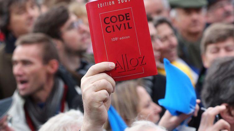 Un manifestant contre le projet de loi sur le mariage pour tous brandit un code civil, le 13 janvier 2013 à Paris. (THOMAS SAMSON / AFP)