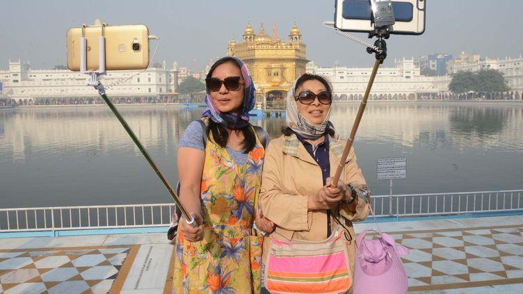 Deux touristes se prennent en photo devant un temple à Amritsar (Inde), le 14 novembre 2016. (NARINDER NANU / AFP)