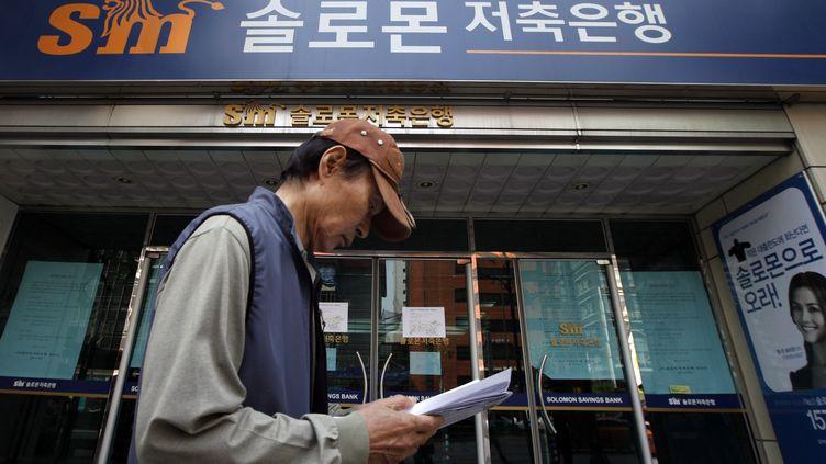 Un homme passe devant une banque Solomon Savings à Séoul (Corée du Sud), le 7 mai 2012. (LEE JAE WON / REUTERS)