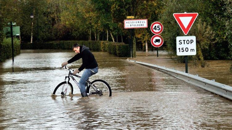 Tentative d'expédition à vélo dans la ville deHesdigneul-les-Boulogne (Pas-de-Calais), touchée par des intempéries, le 2 novembre 2012. (PHILIPPE HUGUEN / AFP)