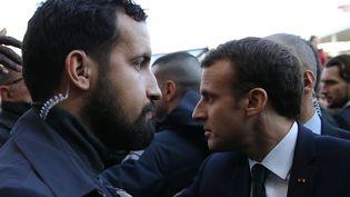 L'agent de sécurité Alexandre Benalla (à gauche) près d'Emmanuel Macron (à droite) lors de l'inauguration du Salon de l'Agriculture, le 24 février 2018, à Paris. (STEPHANE MAHE / POOL / AFP)