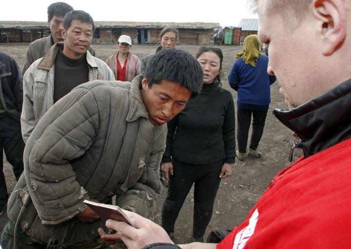 Un officier des services russes d'immigration contrôle les papiers d'un travailleur agricole chinois près de Tvogorovo, dans le kraï (région) de Krasnoïarsk, Sibérie orientale, en 2009. (Reuters/Ilya Naymushin)