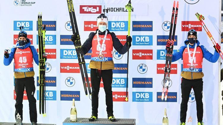 Quentin Fillon Maillet (2e) et Fabien Claude (3e) sur le podium du sprint d'Hochfilzen, derrière le Norvégien Johannes Dale. (JOE KLAMAR / AFP)