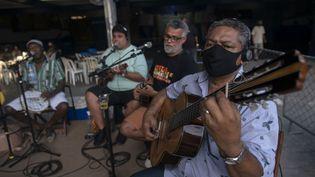 Les musiciens de Samba doTrabalhador en concert auRenascenca club du quartier d'Andarai dans la banlieue de Rio de Janeiro, le 26 octobre 2020, dans le respect des mesures sanitaires due à la pandémie de coronavirus. (MAURO PIMENTEL / AFP)