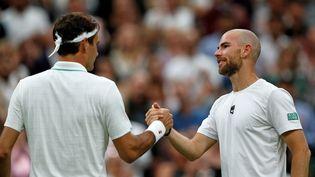 Roger Federer et Adrian Mannarino, à l'issue de leur match à Wimbledon, le 29 juin 2021. (ADRIAN DENNIS / AFP)