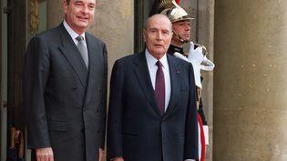 Le président élu Jacques Chirac (à gauche) est accueilli par le président sortant François Mitterrand (à droite), sur le perron de l'Elysée avant de pénétrer à l'intérieur du Palais présidentiel pour la cérémonie de passation de pouvoirs, le 17 mai 1995 à Paris.  (PASCAL PAVANI / AFP)