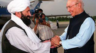 Mohammad Hassan Akhund, le 24 août 1999, lors d'une rencontre avec le ministre des Affaires étrangères du Pakistan, Sartaj Aziz, à Islamabad (Pakistan). (SAEED KHAN / AFP)