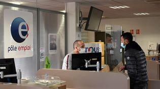Un conseiller Pôle Emploi renseigne une personne à l'agence de Chateau-Gombert à Marseille, le 14 décembre 2020. (NICOLAS TUCAT / AFP)