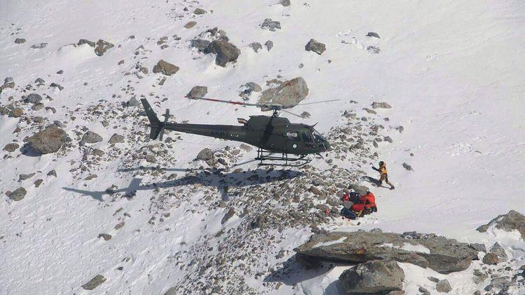 Des secouristes prennent en charge l'alpiniste Elisabeth Revol sur le Nanga Parbat, le 28 janvier 2018. (SAYED FAKHAR ABBAS / AFP)