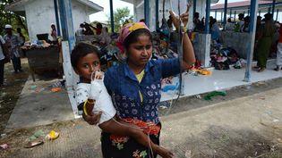 Une femme rohingya portant un enfant, à Kuala Langsa en Indonésie. Image d'illustration. (ROMEO GACAD / AFP)