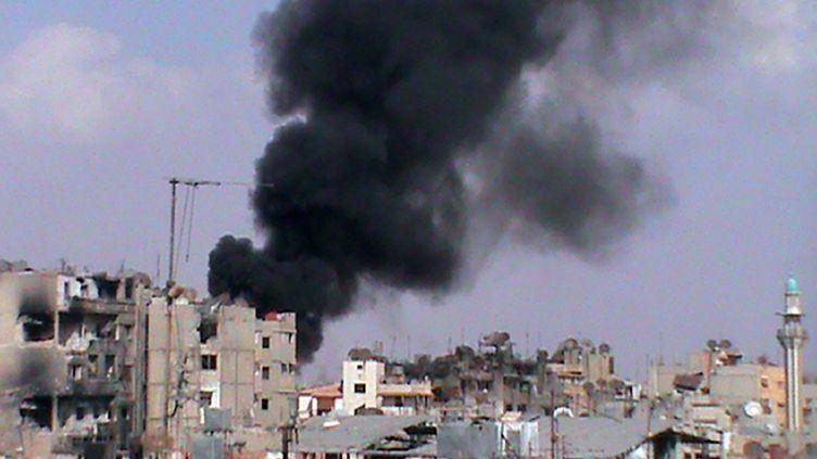 De la fumée noire s'élève au-dessus des maisons de Homs (Syrie), après une explosion, le 9 octobre 2012. (HO / SHAAM NEWS NETWORK / AFP)