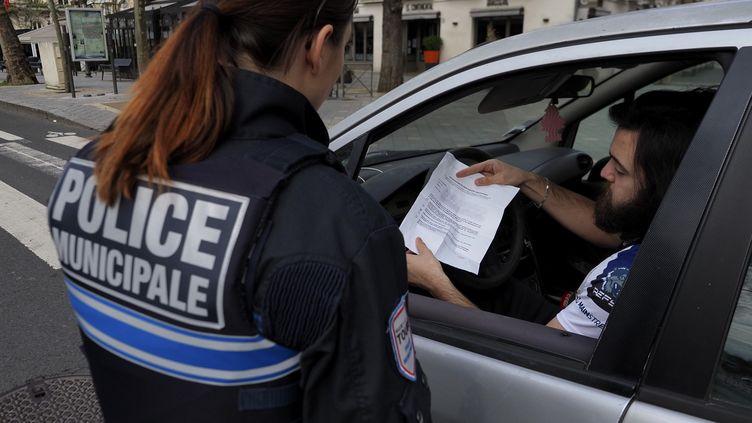 Un automobiliste présente son attestation à la police municipale, le 17 mars 2020, à Tours (Indre-et-Loire). (GUILLAUME SOUVANT / AFP)