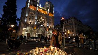 Des personnes allumentdes bougies devant la basilique Notre-Dame de l'Assomption à Nice le 30 octobre 2020. (VALERY HACHE / AFP)