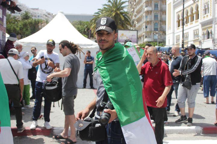 Islam parcourt la place de la Grande Poste avec son appareil photo à la main, le 21 juin 2019, à Alger. (CLEMENT PARROT / FRANCEINFO)