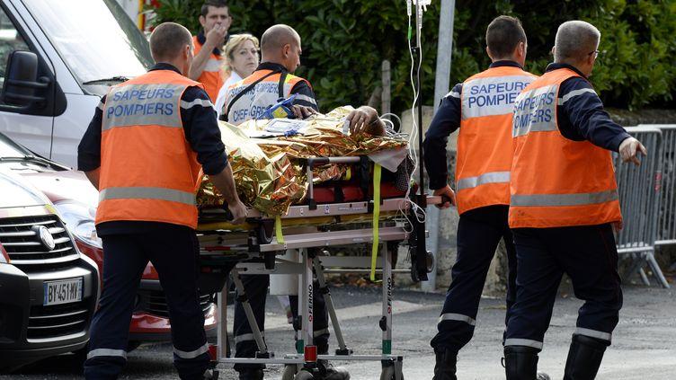 Des secours transportent un blessé à Puisseguin (Gironde), le 23 octobre 2015, après l'accident meurtrier qui s'est produit à la sortie de la commune. (JEAN-PIERRE MULLER / AFP)