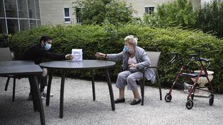 La résidente d'un Ehpad reçoit un cadeau de son petit-fils à l'occasion de la fête des mères à Saint-Maur-des-Fosses(Val-de-Marne), le 7 juin 2020. (ANNE-CHRISTINE POUJOULAT / AFP)