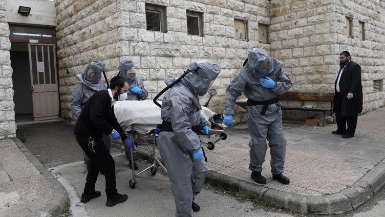 Des employés d'une société de pompes funèbres transportent le corps d'un patient décédé du Covid-19, le 1er avril 2020 à Jérusalem (Israël). (AHMAD GHARABLI / AFP)
