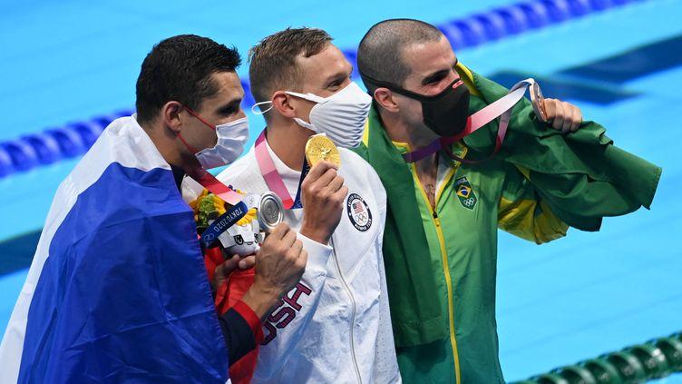 Le podium du 50 mètres nages libre avec, de gauche à droite, Florent Manaudou, Caeleb Dressel et Bruno Fratus, le dimanche 1er août à Tokyo. (JONATHAN NACKSTRAND / AFP)