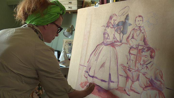"""Nathalie Novi, l'iniatrice du projet de fresque collective, en train de peindre sa """"famille confinée"""",dans son atelier du Jura. (H. Perret / France Télévisions)"""