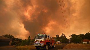 Un camion de pompier stationne sur une route alors qu'un feu brûle à Bargo, au sud-ouest de Sydney, le 21 décembre.Au moins 3 millions d'hectares ont brûlé à travers le pays ces derniers mois dans des incendies qui ont causé la mort de 10 personnes et détruit plus de 800 maisons. (PETER PARKS / AFP)