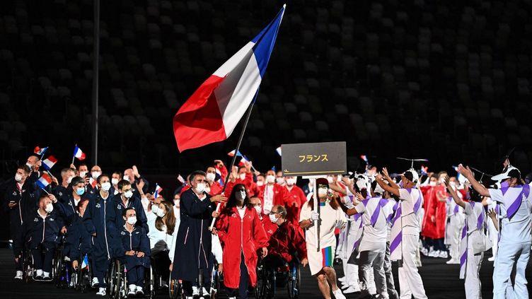 La France a défilé en avant dernier, juste après les États-Unis et avant le Japon, le pays hôte (la France et les États-Unis sont les prochaines nations à accueillir l'événement). La délégation française, emmenée par les deux porte-drapeaux Stéphane Houdet et Sandrine Martinet, a défilé en respectant l'ordre des couleurs du drapeau national. (PHILIP FONG / AFP)