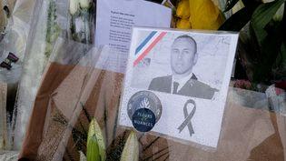 Un portrait du lieutenant-colonel Arnaud Beltrame attaché à un bouquet de fleurs déposé devant la gendarmerie de Carcassonne (Aude), le 25 mars 2018. (ERIC CABANIS / AFP)