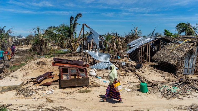 Une femme marche devant une maison détruite par le cyclone Kenneth, sur l'île d'Ibo au Mozambique, le 13 mai 2019. (ZINYANGE AUNTONY / AFP)
