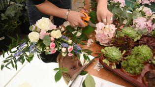 Une fleuriste en train d'élaborer un bouquet. (OLI SCARFF / AFP)