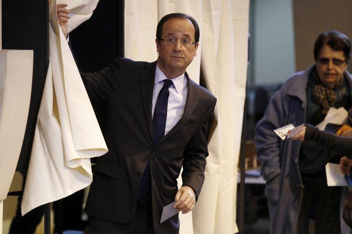 François Hollande sort de l'isoloir un bulletin de vote à la main, à Tulle (Corrèze), le 22 avril 2012. ( JACKY NAEGELEN / REUTERS)
