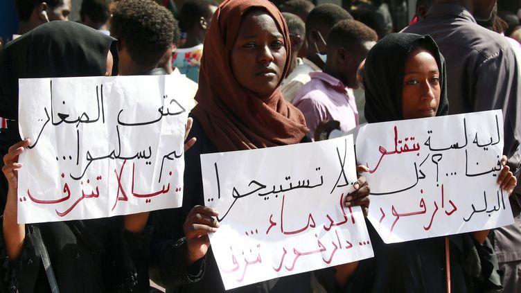 """Des habitants du Darfour ont protesté à Khartoum, le 23 septembre 2019, contre la violence dont a fait usage la police pour réprimer des centaines d'étudiants manifestant contre la pénurie de pain dans la ville de Nyala. """"Pourquoi continuez-vous à nous tuer"""" et """"le Darfour saigne"""" affirment les pancartes brandies par ces manifestantes. (ASHRAF SHAZLY / AFP)"""