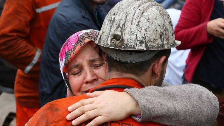 Une femme prend dans ses bras un secouriste qui tente de sauver des personnes encore bloquées dans la mine de Soma (Turquie), le 14 mai 2014. (EMIN MENGUARSLAN / ANADOLU AGENCY / AFP)
