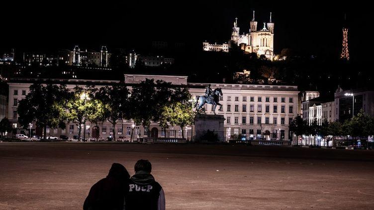 Deux adolescents profitaient de leurs derniers instants dehors quelques minutes avant le couvre-feu à Lyon (Rhône), le 17 octobre 2020. (JEFF PACHOUD / AFP)