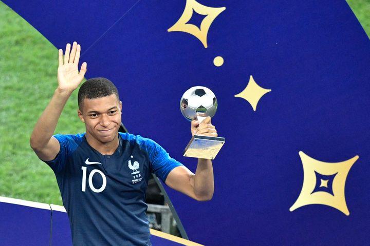 L'attaquant des Bleus, Kylian Mbappé, soulève son trophée du meilleur jeune de la Coupe du monde, dimanche 15 juillet 2018 à Moscou (Russie). (ALEXANDER NEMENOV / AFP)