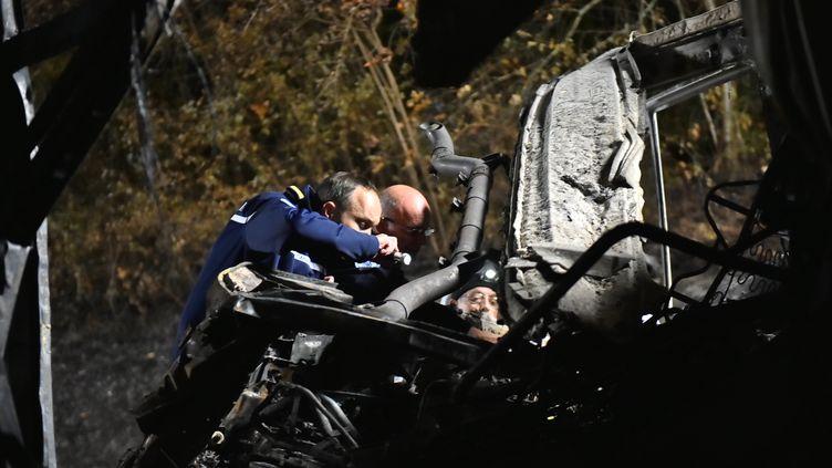 Des gendarmes examinent la carcasse du car impliqué dans l'accident de Puisseguin (Gironde), le 23 octobre 2015. (JEROME GROISARD / MINISTERE DE L'INTERIEUR / AFP)