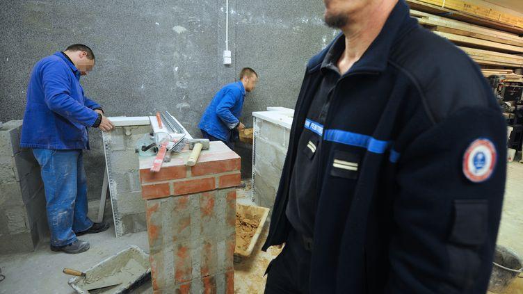 Des détenus travaillent dans le cadre d'un stage de formation professionnelle en bâtiment, le 2 novembre 2011 au centre pénitentiaire de Nantes (Loire-Atlantique). (FRANK PERRY / AFP)