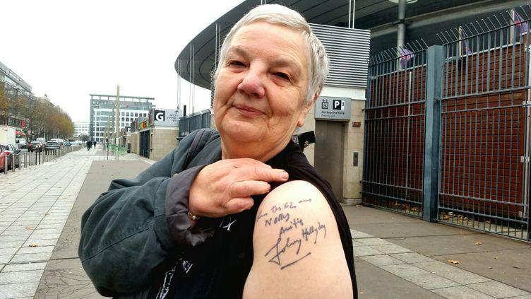 Nelly, 66 ans, le 6 décembre devant le Stade de France. Elle s'est fait tatouer une dédicace de Johnny Hallyday. (BENJAMIN ILLY / RADIO FRANCE)