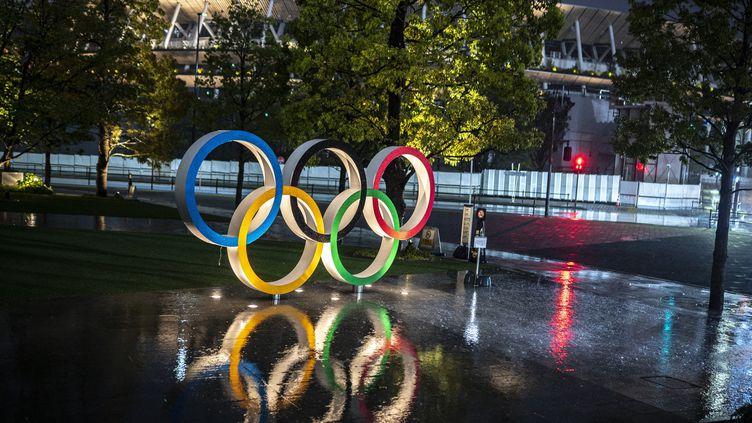 Les anneaux des Jeux olympiques sont éclairés à Tokyo (Japon), le 14 avril 2021. (CHARLY TRIBALLEAU / AFP)