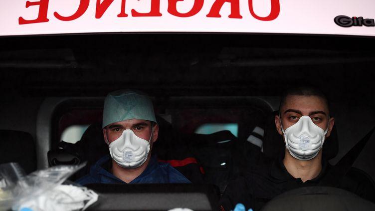Des pompiers équipés de masques lors de la prise en charge d'un patient atteint du Covid-19, le 24 mars 2020 à Paris. (FRANCK FIFE / AFP)