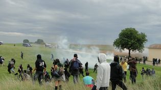 Bloqués par plusieurs gendarmes mobiles à la sortie du village de Saudron (Haute-Marne), des opposants au projet Cigéo ont monté une rapide barricade quand d'autres sont allés dans le champ d'à côté, le 16 août 2016. Avec les premiers jets de grenades lacrymogènes. (MAXPPP)