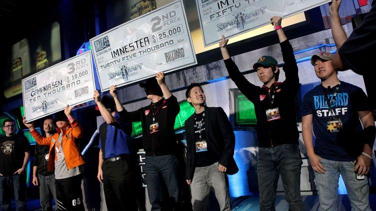 """De gauche à droite, les joueurs """"GamaniaSen"""", """"Nestea"""", et """"MVP"""", brandissent leurs chèques de récompense après la finale de la compétition Global Starcraft II, organisée le 22 octobre 2011 à Anaheim (Californie). (DEREK BAUER / AP / SIPA)"""