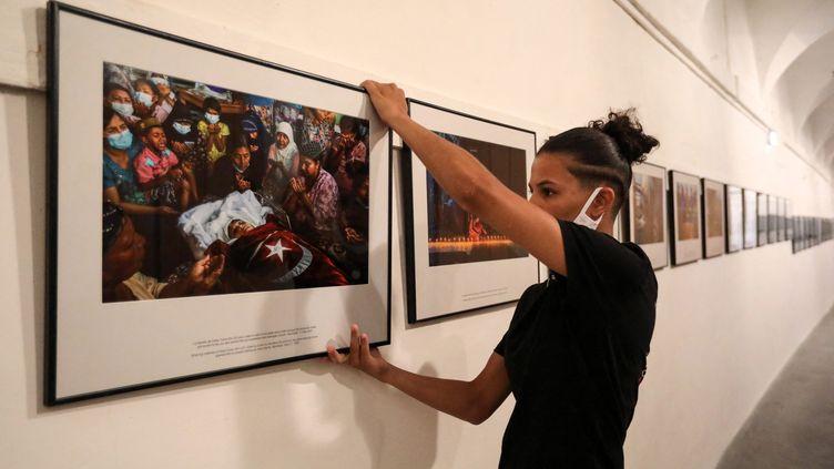 """Accrochage de l'exposition """"La révolution du printemps en Birmanie"""" réalisée par un photographe qui a tenu à rester anonyme, à la 33e édition du festival Visa pour l'Image à Perpignan, le 25 août 2021. (RAYMOND ROIG / AFP)"""