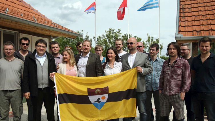 Le président autoproclamé de la «République libre du Liberland» Vit Jedlička (au centre, en costume vert foncé) pose avec son épouse, quelques-uns de ses futurs concitoyens et le drapeau de la nouvelle micronation. Bački Monoštor, Serbie, 1er mai 2015. (REUTERS/Antonio Bronic TPX IMAGES OF THE DAY )