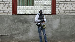 Un homme armé et cagoulé garde le siège de la police à Slaviansk, le 12 avril 2014, dans l'est de l'Ukraine. (GLEB GARANICH / REUTERS)