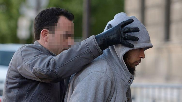 Un policier escorte, le 29 mai 2015, Alexandre Dhaussy, soupçonné d'avoir attaqué au couteau un militaire à la Défense. (ERIC FEFERBERG / AFP)