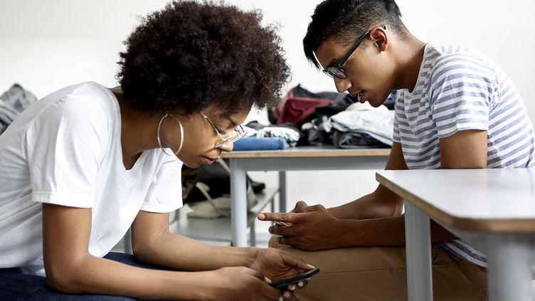 Des adolescents regardant leur téléphone dans une salle de classe (illustration). (DINOCO GRECO / MAXPPP)